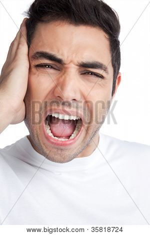 Young man yelling and covering ears isolated on white background.