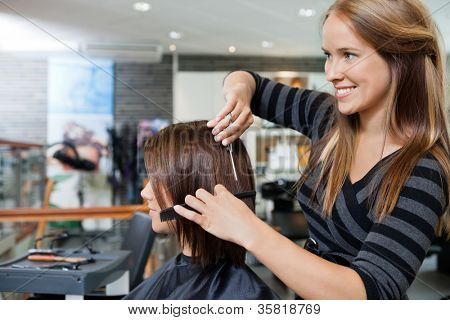 Beautiful young hairdresser giving a new haircut to female customer at parlor