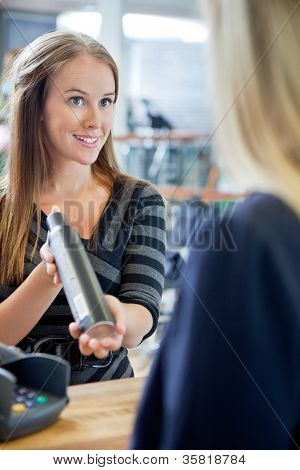 Young female hairstylist showing hair product to customer at counter