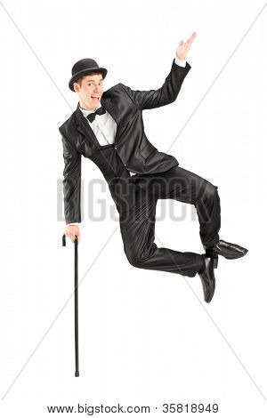 Magician jumping and holding a cane, isolated on white background