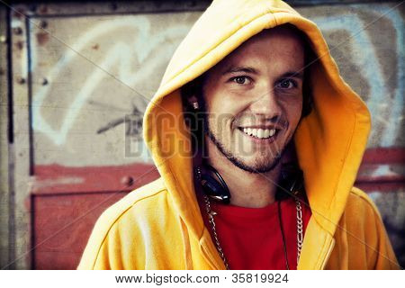Young man portrait in hooded sweatshirt / jumper on grunge graffiti wall