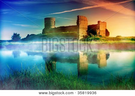 Old castle ruins at magical sunset at the river. Poland, Europe.