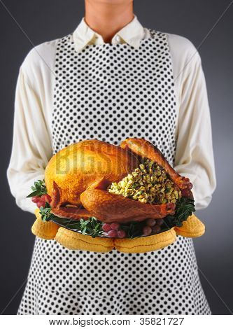 Closeup of a homemaker in an apron and oven mitts holding a platter with a roasted turkey. Horizontal format over a light to dark background. Woman is unrecognizable. Shallow depth of field.