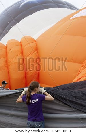 READINGTON, NJ-JUL 29: Crew members hold the material to help inflate the Quick Chek Cosmic Q balloon at the Quick Chek New Jersey Festival of Ballooning on July 29, 2012 in Readington, NJ.