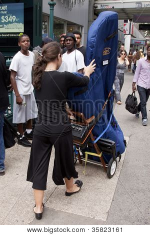 NEW YORK-JUL 28: Emily Hopkins transports her harp along 34th St to Penn Station on July 28, 2012 in New York, NY. She is on MTA'Ã??Ã??s official roster for the transit talent program Music Under New York.
