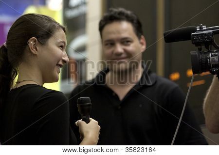 NEW YORK-JUL 28: Harpist Emily Hopkins is interviewed in Penn Station while her father  Rich Hopkins smiles on July 28, 2012 in New York, NY. She is on MTA'Â?Â?s official roster for Music Under New York.