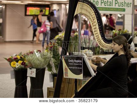 NEW YORK-JUL 28: Harpist Emily Hopkins performs in Penn Station while commuters walk by on July 28, 2012 in New York, NY. She is on MTA's official roster for the Music Under New York program.