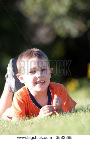 Cute Boy Outside On His Stomach In The Grass