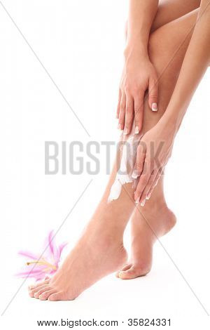 Woman applying cream on her legs over white background