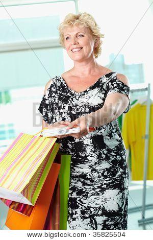 Retrato de mulher envelhecido médio com paperbags dando dinheiro no centro de comércio