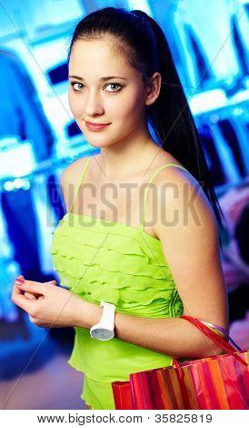 Retrato de uma mulher bonita com paperbags olhando para câmera no departamento de vestuário
