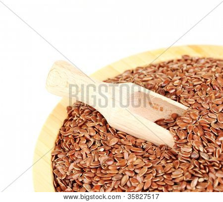 flax seeds in wooden bowl with spoon on white background close-up