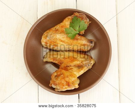 roasted chicken wings with parsley in the plate on white wooden background close-up