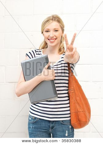picture of smiling teenage girl with laptop showing victory sign