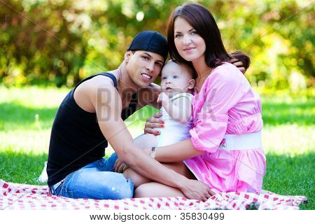 Happy family relaxing in park at summer day