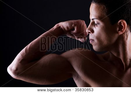 Muscular man showing his strong biceps over white background