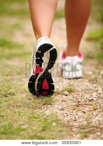 Closeup of female legs jogging on a trail