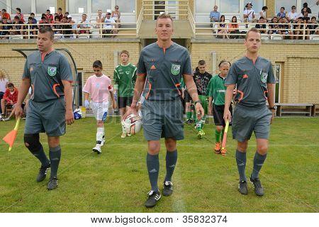 KAPOSVAR, HUNGARY - JULY 21: Competitors march in into the stadium at the VIII. Youth Football Festival U14 match Tirgu Mures (pink) (ROM) vs. Kaposvar (green)(HUN) on July 21, 2012 in Kaposvar, Hungary