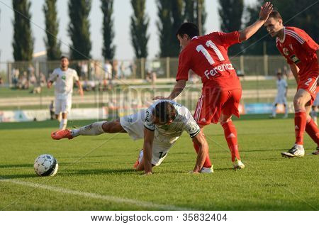 KAPOSVAR, HUNGARY - AUGUST 4: Lorant Olah (in white) in action at a Hungarian National Championship soccer game Kaposvar (white) vs Debrecen (red) on August 4, 2012 in Kaposvar, Hungary.