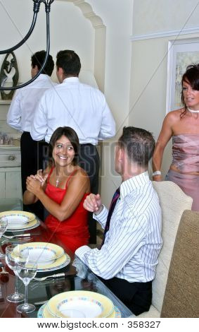 Smartly Dressed Guests Sitting At The Table During A Dinner Part