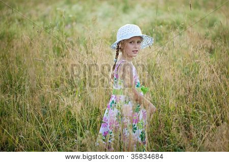 Girl in summer dress among the tall grass