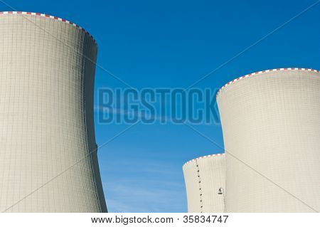 Nuclear power plant cooling towers against a blue sky