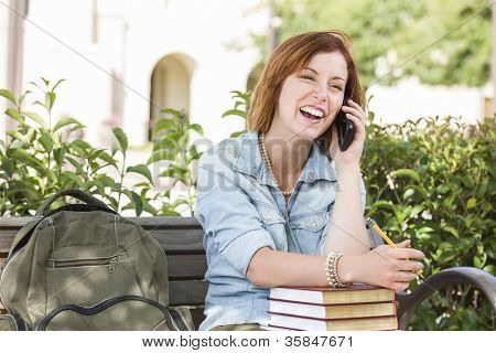 Smiling Young Pretty Female Student Outside on Cell Phone with Backpack and Books Sitting on Bench.