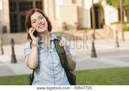 Smiling Young Pretty Female Student with Backpack Walking Outside Using Cell Phone.