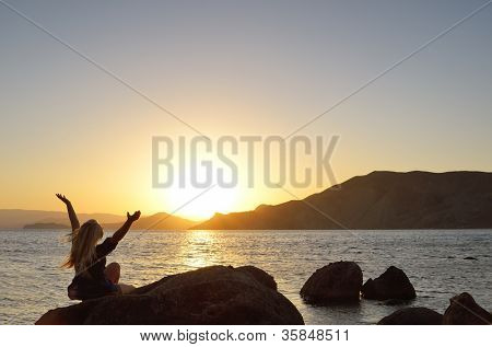 Girl raised her hands to the sky by the sea