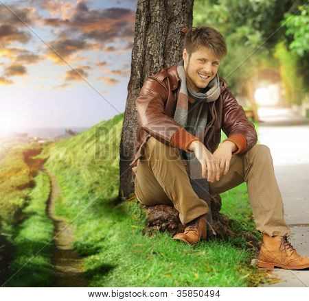 Young stylish happy man in autumn clothing leaning against tree next two path fading off in the distance