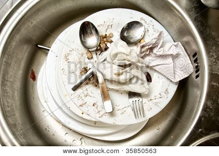 Spoons and fork  on dirty dishes in the kitchen sink