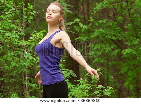 Young beautiful woman with closed eyes doing yoga meditation in forest outdoors