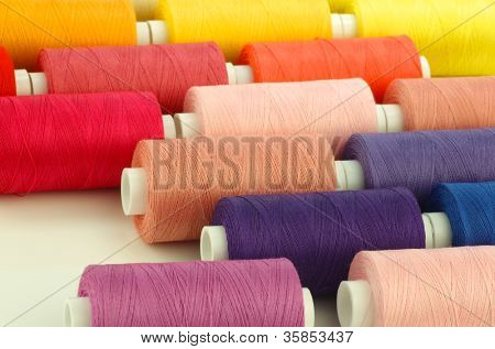 colorful spindles of yarn on a white background