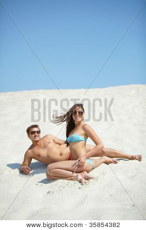 Young couple resting on the sand and looking at camera