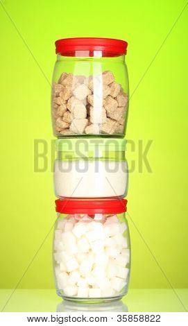 Jars with brown cane sugar lump, white crystal sugar and white lump sugar on colorful background