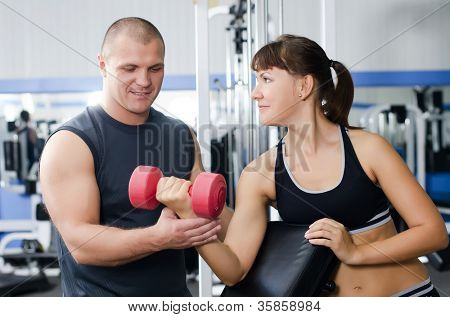 The woman with trainer in sports club