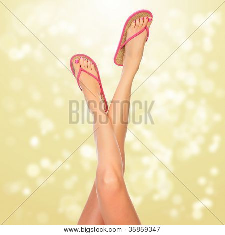 Female legs with pink flip-flops, blurred lights on background