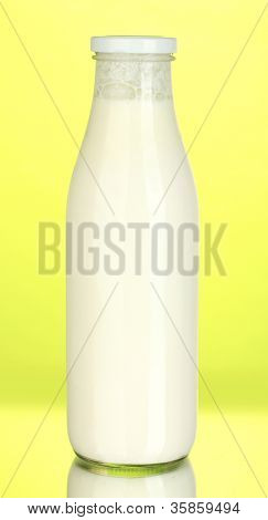 bottle of milk on yellow background close-up