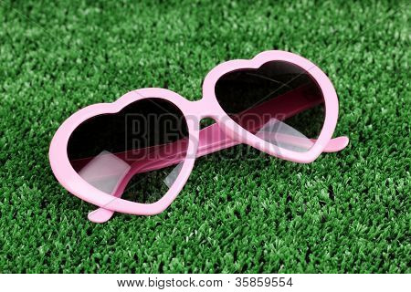 Pink heart-shaped sunglasses on green grass
