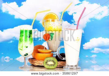 Delicious milk shakes with fruit on wicker cradle on sky background
