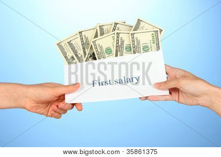 Woman's hand passes the envelope with the salary on blue background