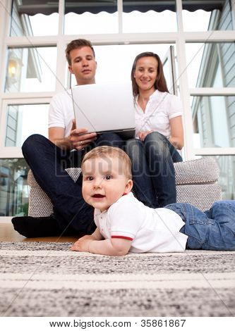 Mother and Father on computer with young son on floor