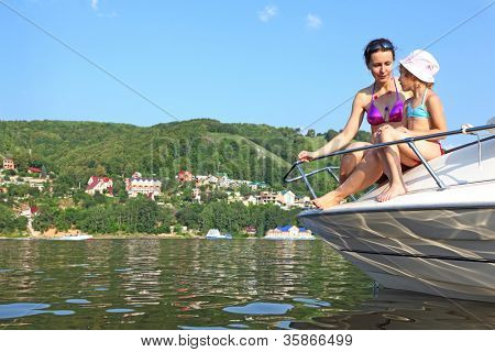 Mother daughter sunbathing and talking on cutter on river, mother look on daughter