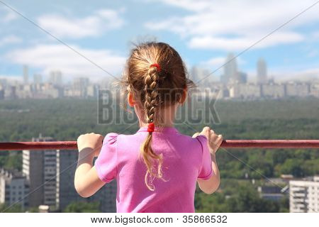 Little girl stand of roof of high building look on city, back
