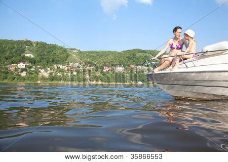 Mother daughter sunbathing on cutter on river