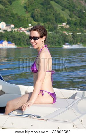 Young woman in glasses sunbathing on cutter on river