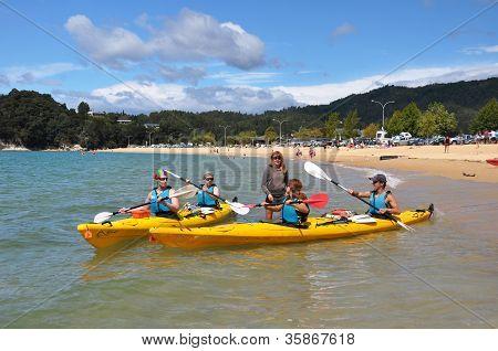 Jovens aprendendo a caiaque na praia de Kaiteriteri, Nova Zelândia