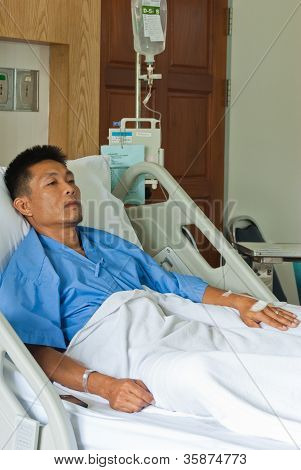 A Patient With Saline Intravenous (iv) On Hospital Bed