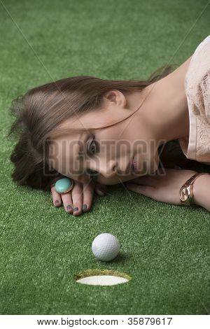 Girl's Lying On Grass With Golf Ball, She Looks The Ball