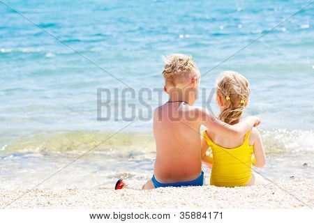 Siblings relaxing on the coast of the sea